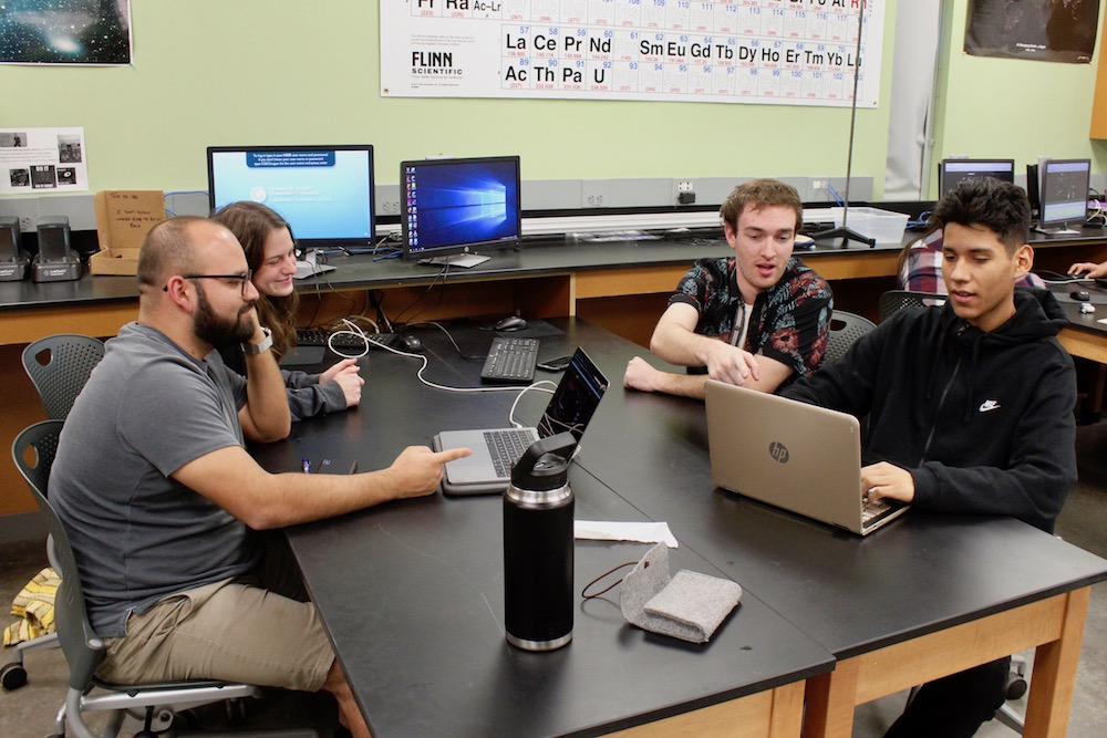 Students at a table working together to solve a complex project on their computers