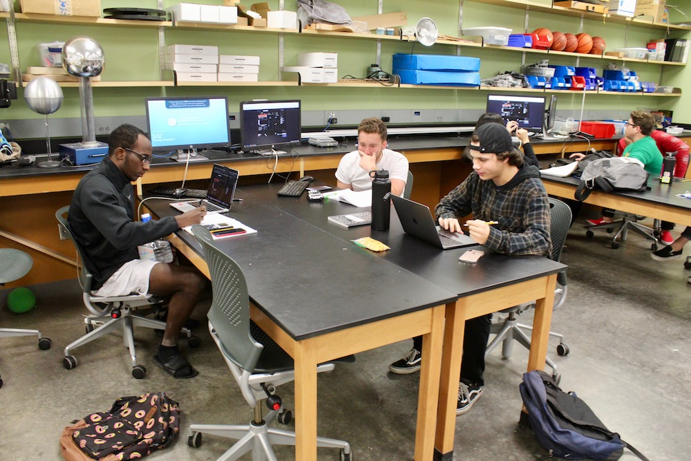 Students at a table working together on a complex project on the computer