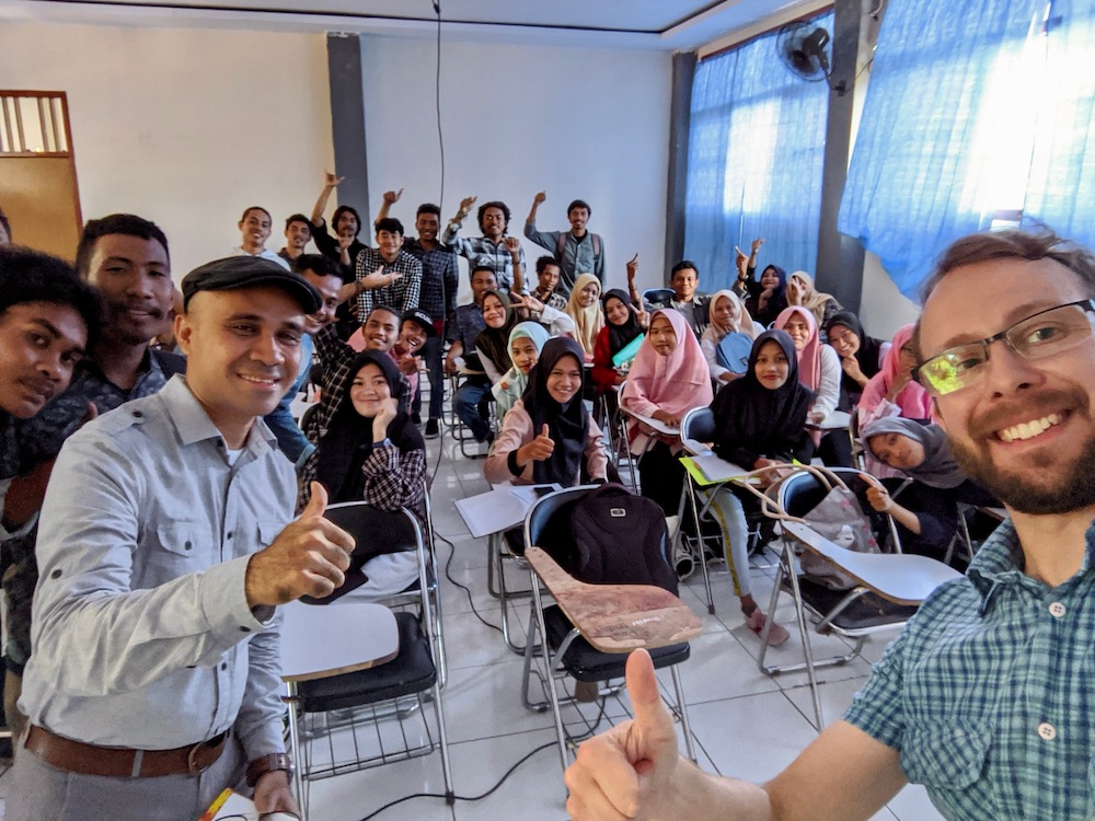 Lev and Halik with a class of Indonesian students, enthusiastically smiling at the camera